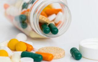 Grønne og gule piller på et bord og i glas
