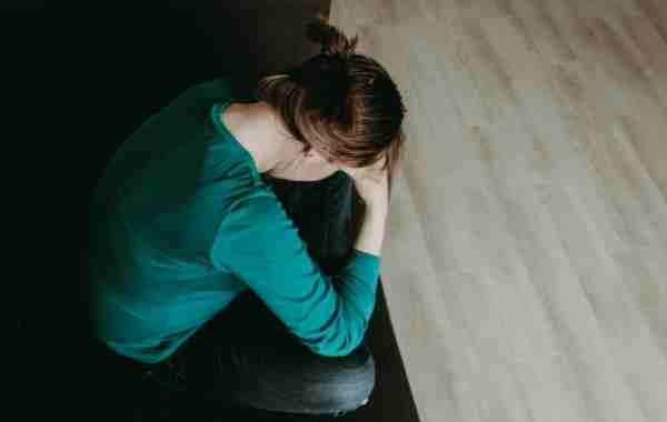 Nedtrykt kvinde sidder ved bord